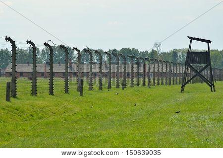 OSWIECIM POLAND - MAY 12 2016: Block of concentration camp Auschwitz Birkenau II behind the fence of barbed wire in Brzezinka Poland.