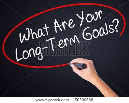 Woman Hand Writing What Are Your Long-term Goals? With A Marker Over Transparent Board