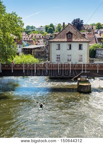 Bamberg Germany - May 22 2016: Canoeist on the River Regnitz against the background of the bridge and the architecture of the old town of Bamberg Bavaria Germany Europe.