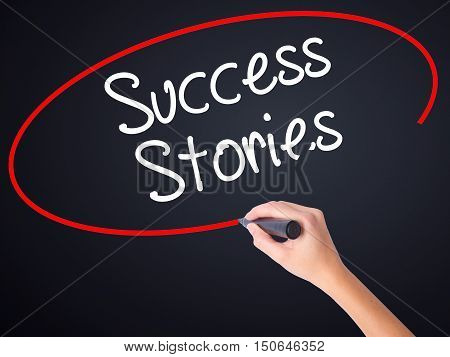 Woman Hand Writing Success Stories With A Marker Over Transparent Board