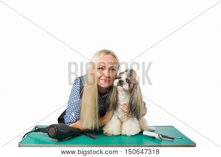 Beautiful smiling woman groomer with funny and cute shih-tzu dog - isolated on white