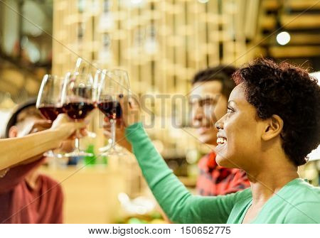 Group of multi ethnic friends cheering and toasting wine in wood wine beer shop - Young cheerful people drinking and having aperitif in bar restaurant - Warm filter