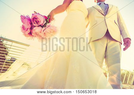 Young newlyweds with bouquet at sunset backlight - Wedding couple together after ceremony - Life and love concept with groom and bride - Lower view point composition with vignetted lomo retro filter