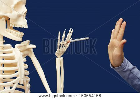 Death offers man a cigarette. Person raised his hand in a negative gesture. Person avoiding smoking.