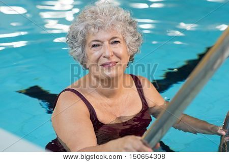 Smiling active senior woman entering in a swimming pool. Smiling old woman looking at camera before the water aerobics lesson. Happy mature woman ready to swim.
