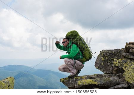 Happy tourist looks into the distance. Happy hiker winning reaching life goal success freedom and happiness achievement in mountains.Concept of success