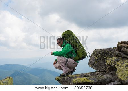 Happy hiker winning reaching life goal success freedom and happiness achievement in mountains. Hiker with backpack on top of a mountain.Concept of success