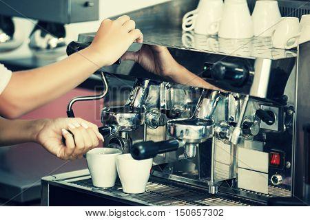 Barista making two espressoes on coffee machine.