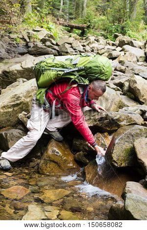 Hiker bending to take a drink from the mountains stream in countryside. Man drink water from river in the wild. The concept of healthy lifestyle. Man taking water from mountain spring on hiking trip
