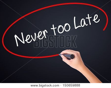 Woman Hand Writing Never Too Late With A Marker Over Transparent Board