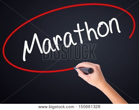 Woman Hand Writing Marathon With A Marker Over Transparent Board .