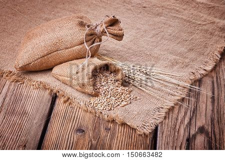 Fresh bread, baked goods, harvest on the farm, delicious food, ears of wheat, burlap sack of grain, healthy food, a table of old wood, wheat grain spillage