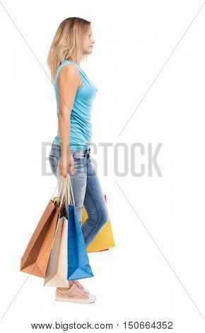 back view of going  woman  with shopping bags . beautiful girl in motion.  backside view of person.  Rear view people collection. Isolated over white background.  The blonde in a blue sweater misses