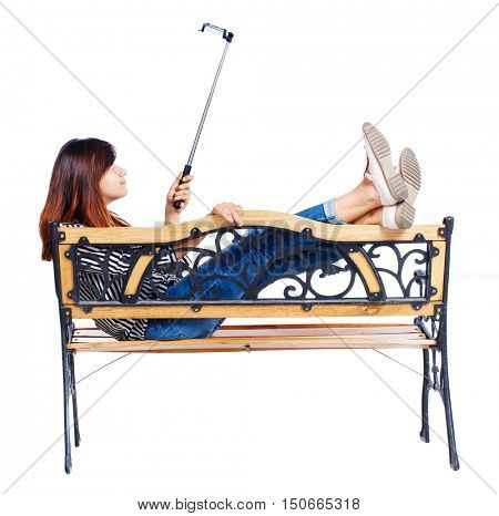 Back view of a woman to make a selfie stick portrait sitting on the bench. girl watching. Rear view people collection. backside view of person. Isolated over white background. girl lying on a bench