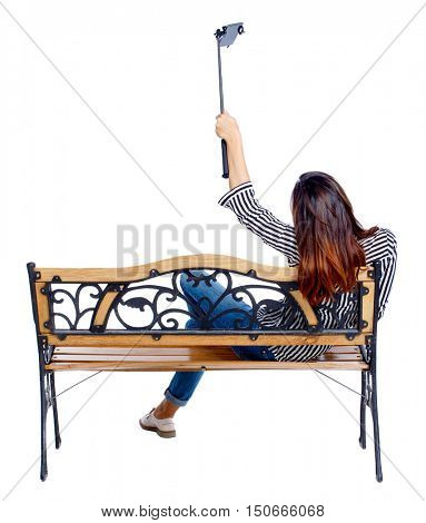 Back view of a woman to make a selfie stick portrait sitting on the bench. girl watching. Rear view people collection. backside view of person. Isolated over white background. Girl on a bench in the