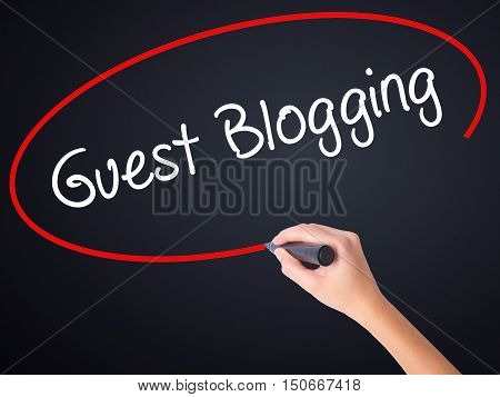 Woman Hand Writing Guest Blogging  With A Marker Over Transparent Board