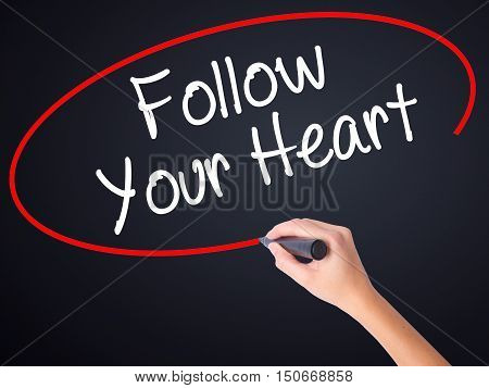 Woman Hand Writing Follow Your Heart With A Marker Over Transparent Board
