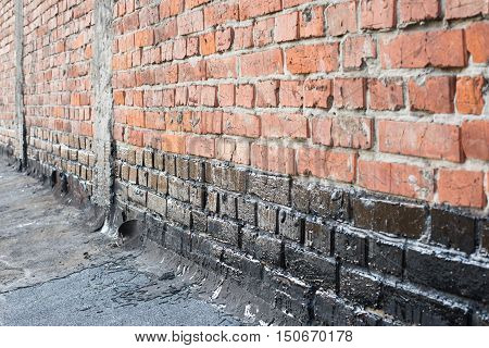 Covered brick wall bitumen primer for improving adhesion during surfacing contiguity with rolled waterproofing during the installation of flat roof.