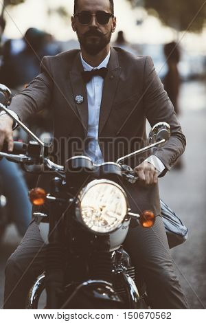 ALICANTE SPAIN - SEPTEMBER 25 2016: Portrait of a bearded young man is riding motorcycle on the Distinguished Gentleman's Ride day a global fundraiser for prostate cancer and men's health investigation.