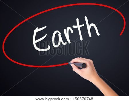 Woman Hand Writing Earth With A Marker Over Transparent Board .