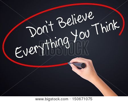 Woman Hand Writing Don't Believe Everything You Think With A Marker Over Transparent Board .