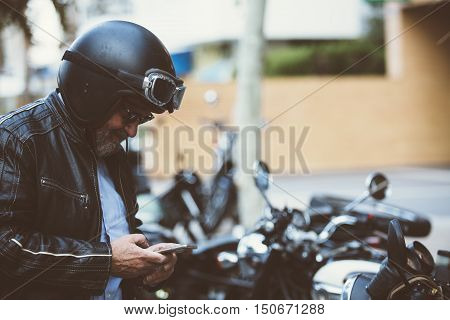 ALICANTE SPAIN - SEPTEMBER 25 2016: Middle aged man is using a smart phone while sitting on his motorbike on the Distinguished Gentleman's Ride day a global fundraiser for prostate cancer and men's health investigation