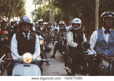 ALICANTE SPAIN - SEPTEMBER 25 2016: Male rider on motorcycle is ready to start the race near a big group of riders and showing their thumbs up on the Distinguished Gentleman's Ride day a global fundraiser for prostate cancer and men's health investigation