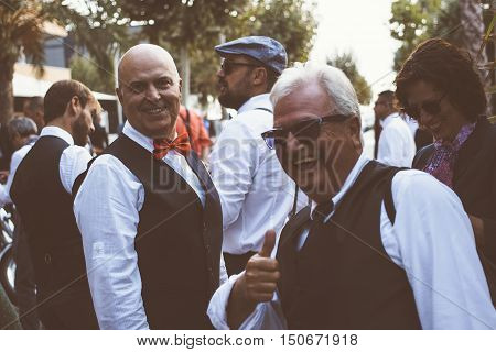 ALICANTE SPAIN - SEPTEMBER 25 2016: Smiling middle aged man is looking at camera while his friend is showing the thumb up on the Distinguished Gentleman's Ride day a global fundraiser for prostate cancer and men's health investigation