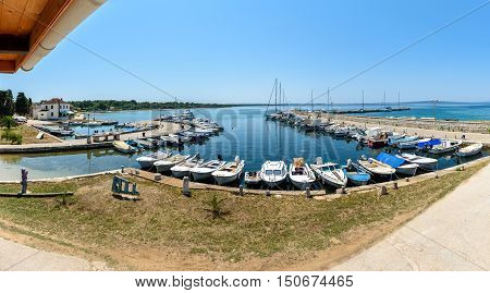 Olib Croatia - July 11 2016: A view from a bar at the small port of Olib Croatia on a beautiful sunny day. Sailboats fishing boats and turist boats are moored a the pier.