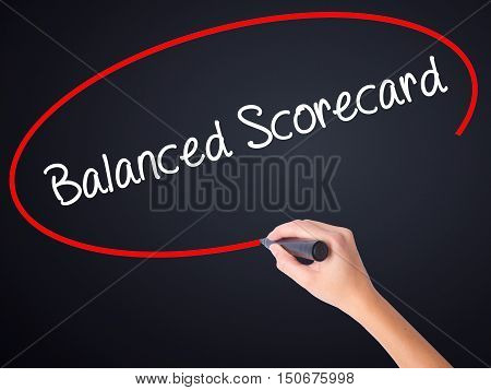 Woman Hand Writing Balanced Scorecard With A Marker Over Transparent Board