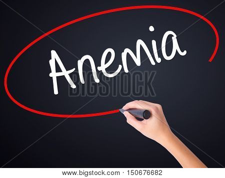 Woman Hand Writing Anemia With A Marker Over Transparent Board .