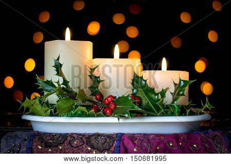 Three descending burning candles with holly and bokeh background in black. Traditional Christmas decoration.