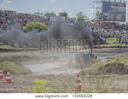 Rostov-on-Don Russia- June 05 2016: Competition for agricultural tractors on the Bizon Track Show.Tractor overcome the water barrier.Spectators watch the races
