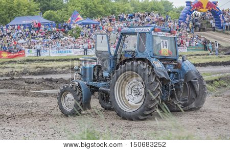 Rostov-on-Don Russia- June 05 2016: Tractor with a damaged wheel on the Bizon Track Show.Spectators watch the races