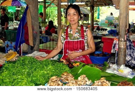 Lamphun Thailand - December 28 2012: Thai woman selling fresh greens and mushrooms at the Mea Tha Covered Market