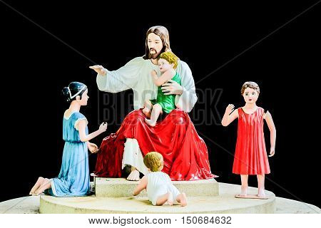 Statues of Jesus and the children isolated on black background.