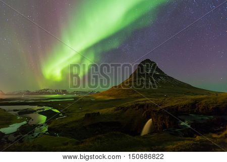 Northern light over Kirkjufell volcano with fully stars on the sky, night view, natural landscape background