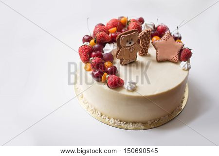 Kids cake with fresh berries and fruits. On the cake figurines of bears and star