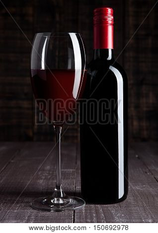 Bottle and glass of red wine on wooden board background