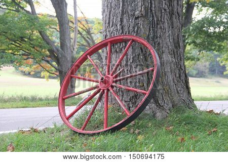 A red wagon wheel against a maple tree in Port Oneida Historic Farm District, Sleeping Bear Dunes National Lakeshore, Michigan