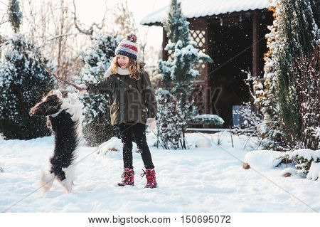 happy child girl playing with her cavalier king charles spaniel dog on the walk in winter snowy garden