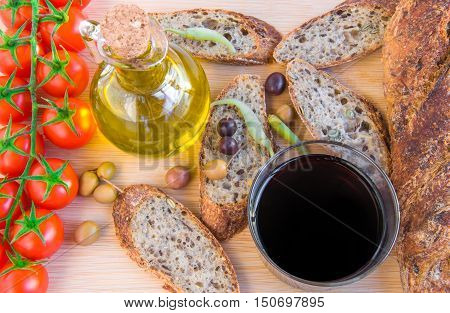 Home baked Alpine baguette olives pepper glass of red vine bottle of olive oil bunch of tomatoes