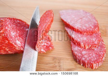 Cutting Salami Slices. Metal Knife Cuts The Salami.