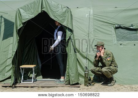Tyumen, Russia - June 11, 2016: Race of Heroes project on the ground of the highest military and engineering school. Cadet holds a radio station and communicates near tent