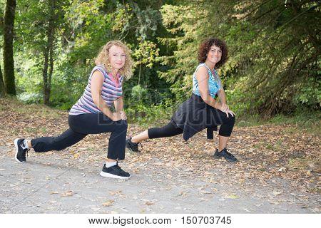 Two Cheerful Sportswomen Stretching And Preparing To Run.