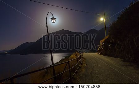 Night landscape with lamps near the road mountains sea and moon are as background. Moon as light of lamp. Village Bali island Crete Greece.