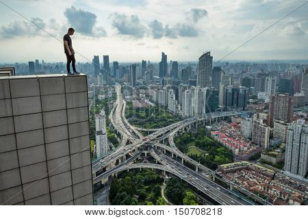 Man stands on edge of roof of tall building and looks at transport interchange in Shanghai, view from K11 building