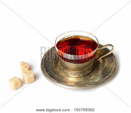 vintage mug with fragrant tea on a metal saucer and sugar on a white background