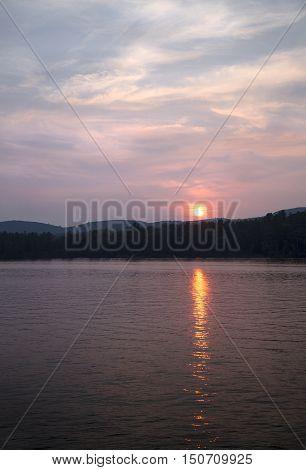 Orange sun setting over Little Squam Lake NH