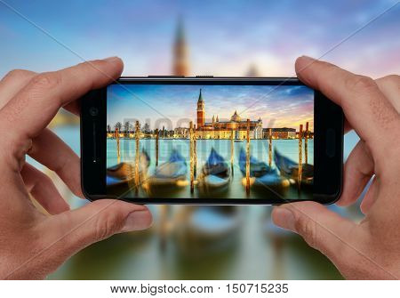 Hands taking picture of Venice, Italy in sunset lights with smartphone camera. Travel concept.